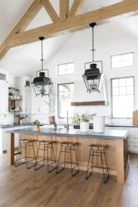 Bright and airy farmhouse style kitchen with exposed beams and pendant lights.
