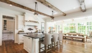 Open floor plan farmhouse style kitchen with exposed beams and beautiful hardwood floors.