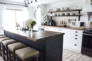 Farmhouse style kitchen with open shelving and a black and white color scheme.