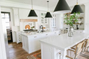 All white farmhouse style kitchen with island and large black hanging lights.